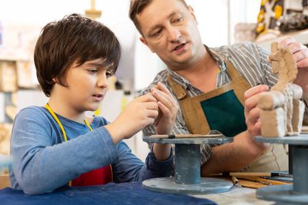 Lección sobre arcilla. Profesor de arte masculino hablando con su alumno creativo inteligente mientras da lecciones sobre arcilla Foto de archivo