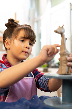 Modeling clay giraffe. Talented dark-eyed beautiful girl modeling clay giraffe at the art lesson