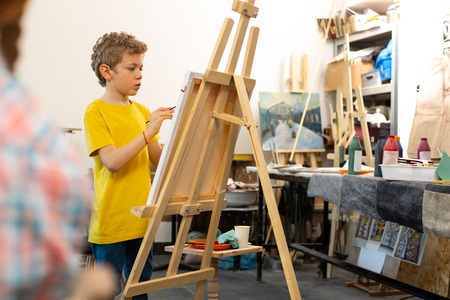 In yellow t-shirt. Blonde-haired talented boy wearing yellow t-shirt painting on drawing easel