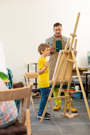 Helping creative pupil. Art teacher wearing apron helping his creative young pupil near drawing easel