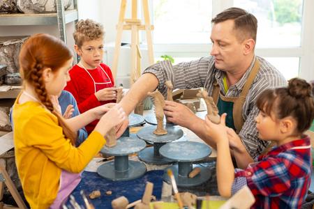 Children sculpting. Talented children listening to teacher and sculpting clay models in workshop