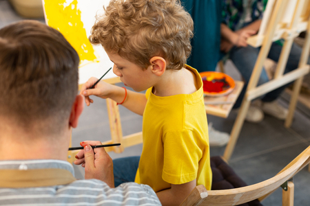 Painting with watercolor. Cute preschool boy feeling good painting with watercolor near teacher
