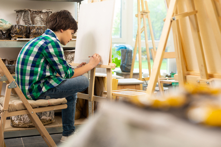 Dark-haired boy. Dark-haired boy wearing squared shirt sitting near painting easel and drawing