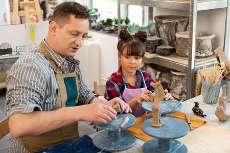 Teacher and girl. Teacher and cute dark-haired girl sculpting little clay animals in art school