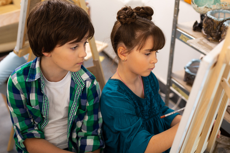 Brother and sister. Dark-haired handsome brother watching his talented sister painting in art school 版權商用圖片