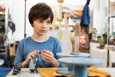 Małe zwierzątko z gliny. Śliczny przystojny utalentowany i kreatywny chłopiec rzeźbi małe gliniane zwierzę w szkole artystycznej Zdjęcie Seryjne