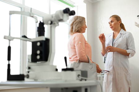 Filled with technique. Diligent long-haired ophthalmologist actively gesturing while talking with calm short-haired woman
