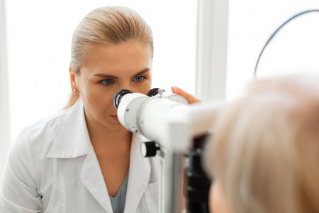 Examining state. Serious blonde lady with blue eyes being a professional ophthalmologist and sitting on checking apparatus