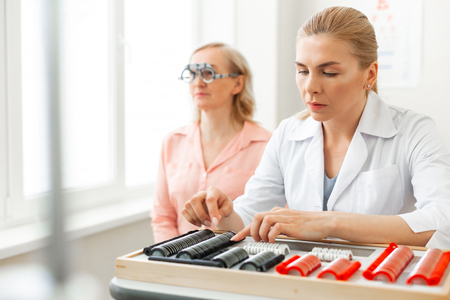 Eye measuring device. Focused woman observing her lens collection in wide case while patient sitting with glasses on