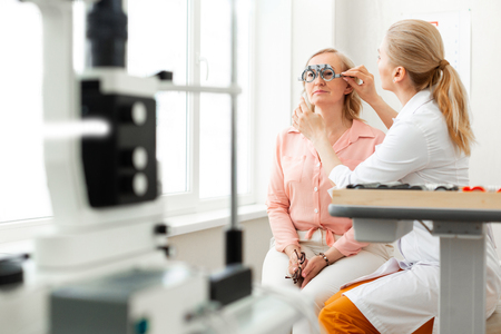 Lens collection. Gentle long-haired doctor correcting placement of glass device while working with patient