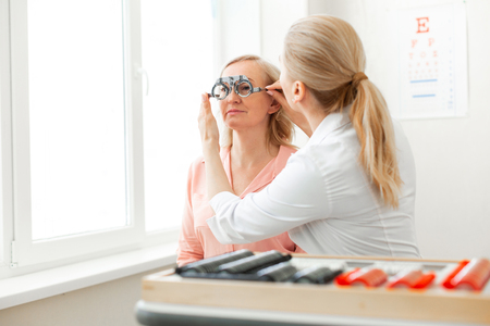 Trabajando con el paciente. Oculista rubio concentrado comprobando el tamaño de la lente necesaria con un dispositivo especial Foto de archivo