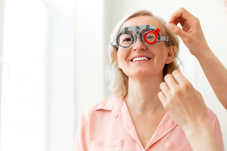 Size of lens. Short-haired patient with wide smile trying on different lenses while having appointment with ophthalmologist