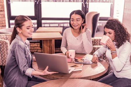 Präsentation anschauen. Zwei schöne dunkelhaarige Frauen trinken Tee, während sie sich die Präsentation ihres Kollegen auf dem Laptop ansehen Standard-Bild