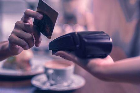Transazione non in contanti. Primo piano di una carta di credito utilizzata per effettuare un pagamento in caffetteria