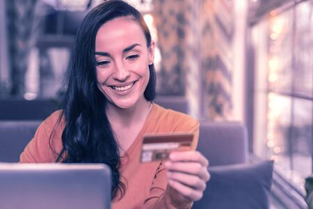 Online shopping. Delighted positive woman looking at her credit card while doing shopping online