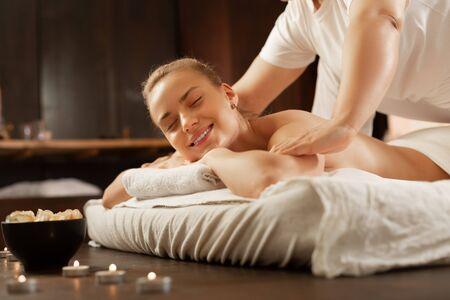 Ervaren massagemeester. Stralende blonde vrouw die in een goed humeur is tijdens massagesessie terwijl bekwame meester op haar lichaam drukt Stockfoto