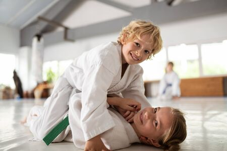 Aikido together. Blonde-haired brother and sister feeling joyful doing aikido together 版權商用圖片