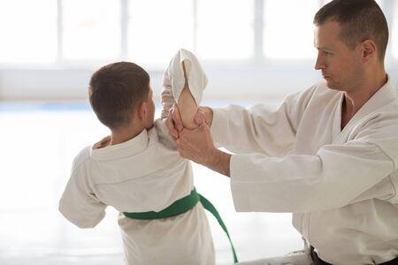 Teaching boy. Professional handsome aikido trainer teaching boy during the lesson 版權商用圖片