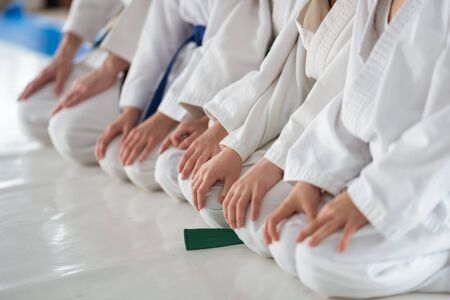 Sitting on floor. Children wearing white kimono sitting on floor and listening to trainer Banco de Imagens