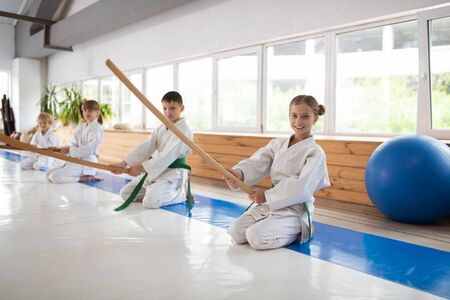 Training together. Girl wearing white kimono sitting near her friends while training together