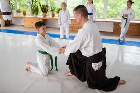 Trainer shaking hands. Aikido trainer shaking hands of his little pupil while supporting him before practicing