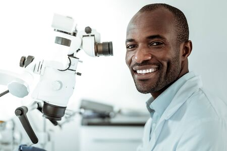 Ordinary workday. African American short-haired beaming doctor openly smiling and showing his ideal white teeth