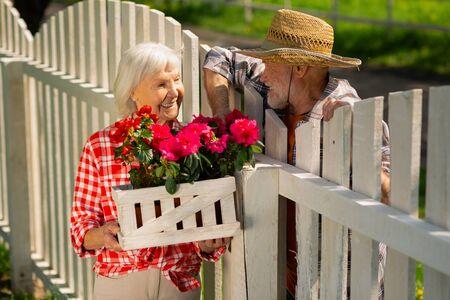 Living in neighborhood. Cheerful retired man and woman living in one neighborhood speaking about flowers Archivio Fotografico