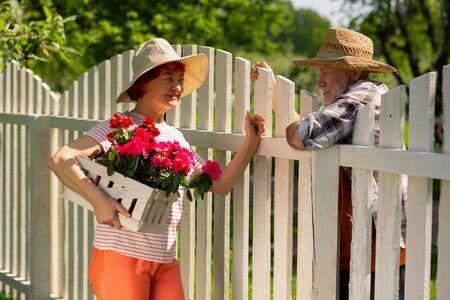 Hablando con el vecino. Mujer de edad pelirroja sosteniendo flores rosadas hablando con el vecino detrás de la valla Foto de archivo