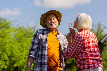 Having fun. Grey-haired wife wearing squared shirt blowing dandelion at husband enjoying summer day Stock Photo
