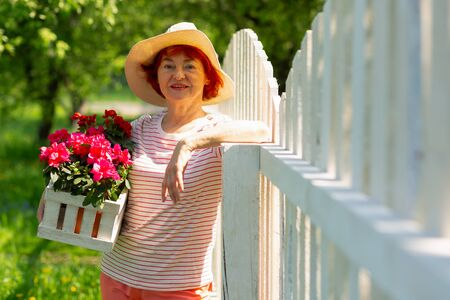 Nice pink flowers. Beautiful aged red-haired woman wearing summer hat holding nice pink flowers