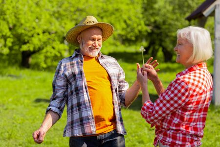 Cheerful pensioners. Cheerful couple of pensioners feeling happy after blowing at dandelion Stock Photo