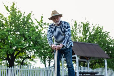 Having some rest. Retired grey-haired man having some rest while holding spade after digging ground
