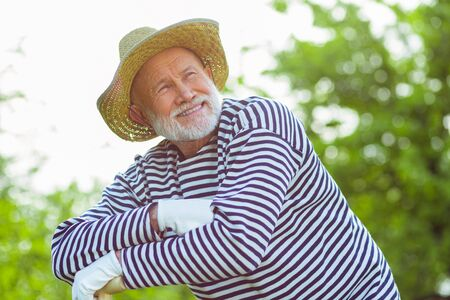 Man feeling happy. Beaming retired man feeling happy spending time near his cottage house