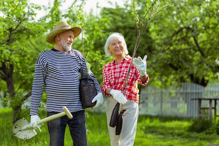 Wife smiling. Loving wife smiling while planting trees together with husband near their cottage husband Stock Photo