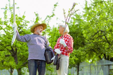 Pensioners laughing. Couple of beaming pensioners laughing before planting trees near their cottage Stock Photo