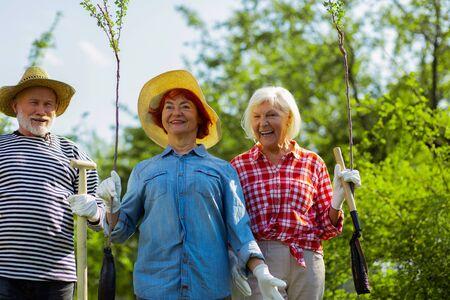 Neighbors feeling excited. Three active retired neighbors feeling excited before planting trees together Standard-Bild