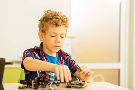 Best hobby. Intelligent cute boy building a robot while being interested in robotics science