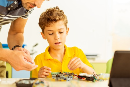 Modern education. Intelligent smart boy sitting in the classroom while constructing a robot