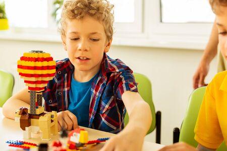Costruire giocattoli. Simpatico ragazzo biondo che prende alcuni dettagli dal set del costruttore mentre costruisce giocattoli