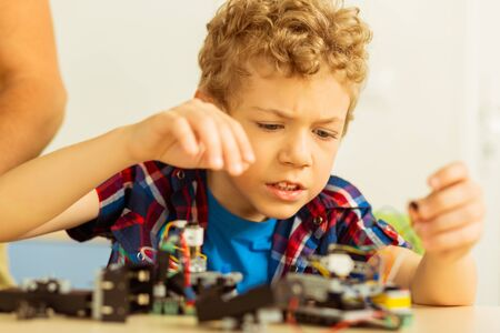 Difficult science. Unhappy cute boy feeling upset while having problems with robot construction Foto de archivo