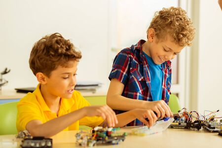 Our common hobby. Happy positive boys having fun while constructing different toys together