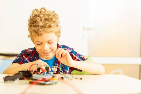Future robot. Happy cute boy looking at the electronic details while trying to create a robot
