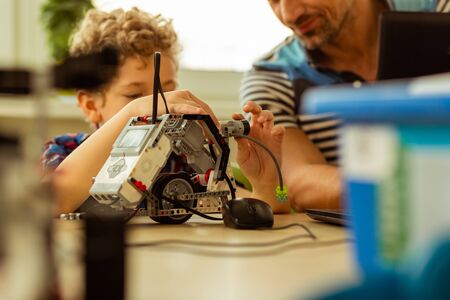 Artificial intelligence. Selective focus of a small robot being constructed by a small cute child