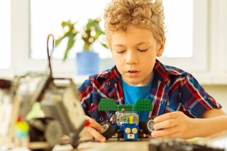 Making a car model. Nice blonde boy holding toy wheels in his hands while making a car model