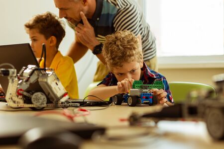 Favourite hobby. Nice young boy sitting at the desk while playing with a car that he constructed Reklamní fotografie