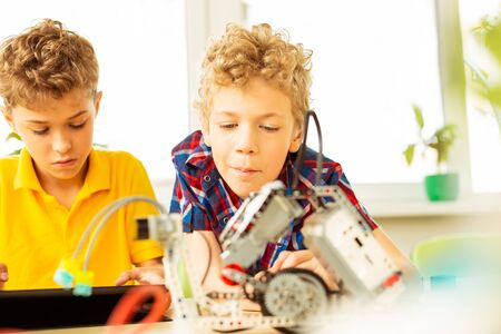 Lesson on robotics. Nice intelligent boys looking at the robot while having a science class on robotics
