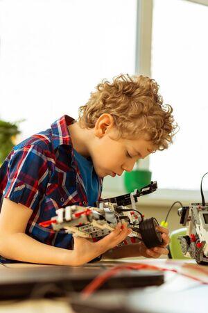 Smart child. Nice smart boy holding a vehicle model while enjoying technical engineering