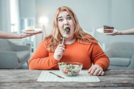 Crazy day. Plump girl staring at camera while eating salad, being on diet