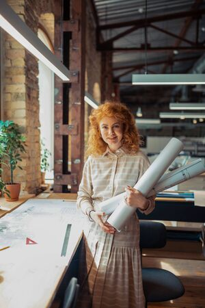 Assistant of interior designer. Curly red-haired assistant of interior designer holding rolls of sketches