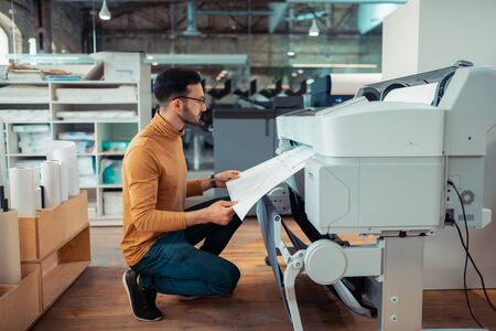 Man waiting. Dark-haired mature man waiting while printing paper with sketches